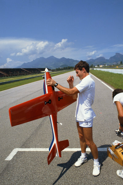 1987 Brazilian Grand Prix. Jacarepagua, Rio de Janeiro, Brazil.10-12 April 1987. Ayrton Senna with one of his remote control planes on the track during testing for the Grand Prix. World Copyright: LAT Photographic.
