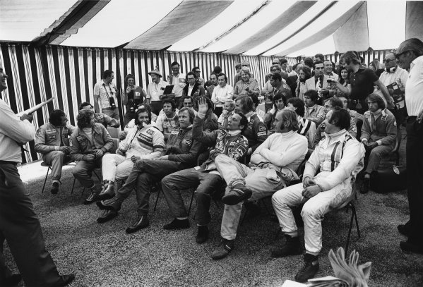 Kyalami, South Africa. 4th - 6th March 1976. Drivers meeting L to R: Gunnar Nilsson, Ian Scheckter, John Watson, Emerson Fittipaldi, Bob Evans, Mario Andretti, Ronnie Peterson, Jochen Mass, Bernard Cahier, Alan Rees, Teddy Mayer, Niki Lauda, James Hunt, LAT Photographer Michael Tee, Michel Leclere, Hans-Joachim Stuck, Tom Pryce, Brett Lunger, Chris Amon, Patrick Depailler, Max Mosley and Jacques Laffite, portrait. World Copyright: LAT Photographic. Ref:  8318 - 33.
