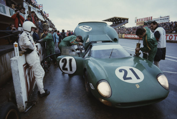 Richard Attwood beside the David Piper Racing, Ferrari 250 LM as mechanics work on the car.