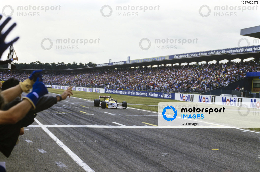 The Williams team celebrates as Nelson Piquet, Williams FW11B Honda, takes the chequered flag.