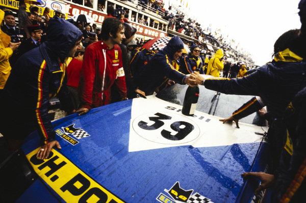 Mechanics pass a bottle of champagne across the bonnet of Claude Ballot-Lèna / Jean-Claude Andruet's Charles Pozzi Ferrari 365 GTB/4 Daytona, the GTS 5.0 class winner.