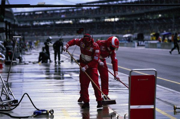 Ferrari mechanics dry up the pit box.