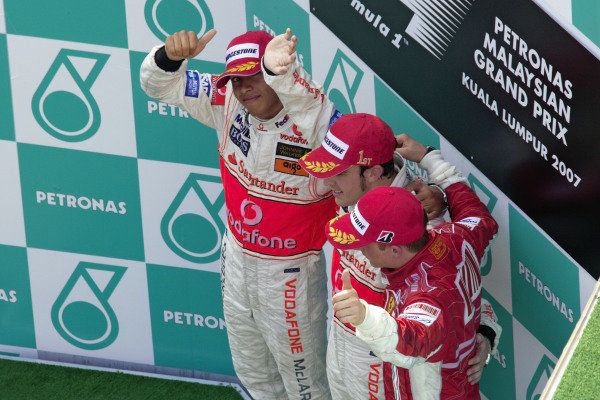Lewis Hamilton, 2nd positon, gives a thumbs up to the camera as teammate Fernando Alonso celebrates his victory and Kimi Räikkönen celebrates a 3rd place.