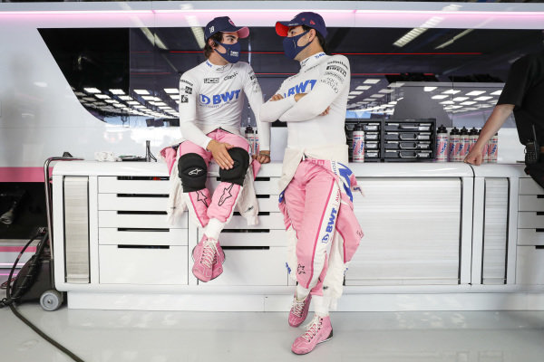 Lance Stroll, Racing Point, and Sergio Perez, Racing Point, talk in the garage