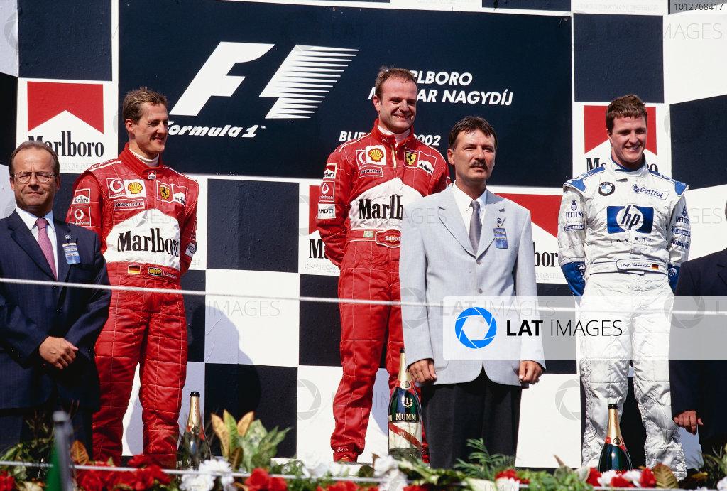 2002 Hungarian Grand Prix.Hungaroring, Budapest, Hungary. 16-18 August 2002.Michael Schumacher (Ferrari) 2nd position, Rubens Barrichello (Ferrari) 1st position and Ralf Schumacher (Williams BMW) 3rd position on the podium. Ref-02 HUN 35.World Copyright - Rose/LAT Photographic