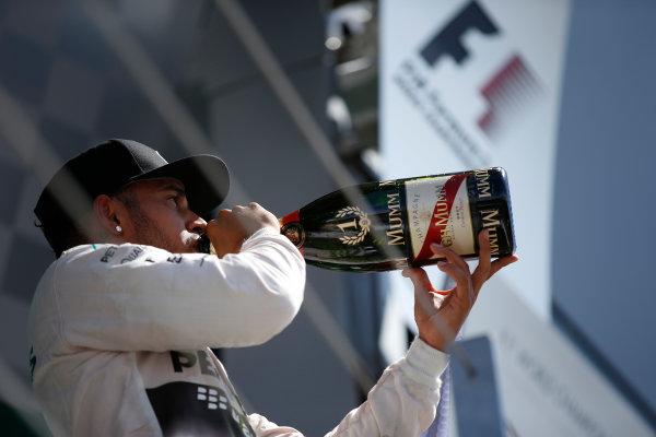 Silverstone Circuit, Northamptonshire, England. Sunday 5 July 2015. Lewis Hamilton, Mercedes AMG, 1st Position, tastes the victory Champagne on the podium. World Copyright: Glenn Dunbar/LAT Photographic ref: Digital Image _89P4150