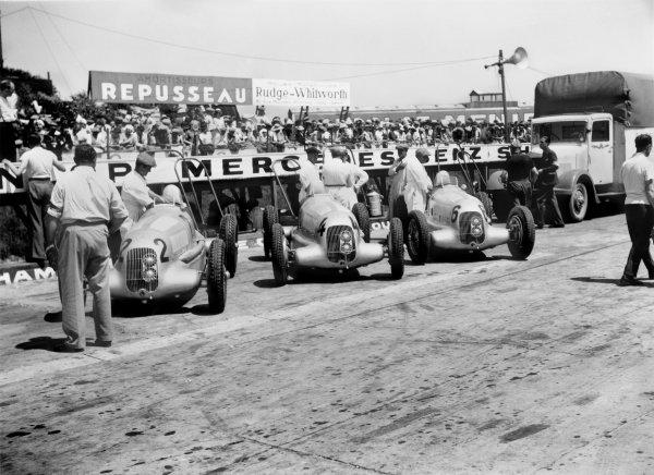 1935 French Grand Prix. Montlhery, France. 23 June 1935. The Mercedes-Benz W25B cars of Rudolf Caracciola, Manfred von Brauchitsch and Luigi Fagioli in the pits, atmosphere. World Copyright: LAT Photographic Ref: Motorsport b&w negative
