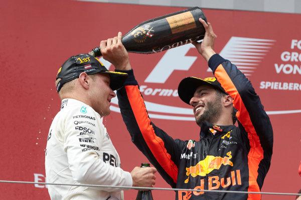 Red Bull Ring, Spielberg, Austria. Sunday 9 July 2017. Daniel Ricciardo, Red Bull Racing, 3rd Position, pours Champagne on Valtteri Bottas, Mercedes AMG, 1st Position. World Copyright: Steve Etherington/LAT Images ref: Digital Image SNE14674