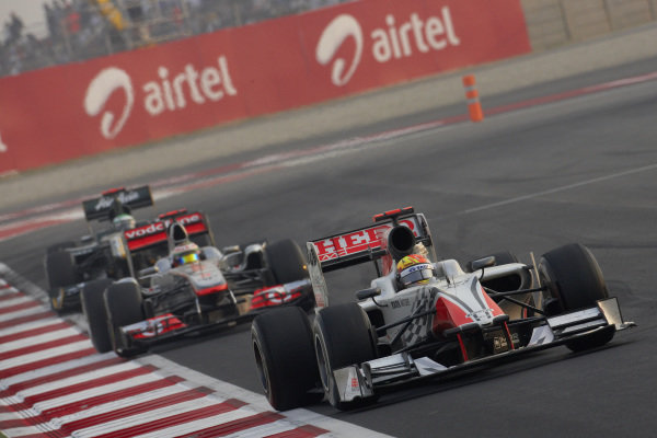 Narain Karthikeyan, HRT F111 Cosworth, leads Lewis Hamilton, McLaren MP4-26 Mercedes, and Heikki Kovalainen, Lotus T128 Renault.
