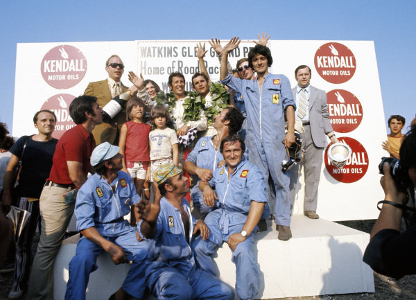 Winners Jacky Ickx and Mario Andretti celebrate victory with their mechanics on the podium.