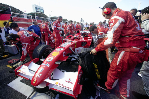 Mechanics get to work on Michael Schumacher's Ferrari 248 F1 making last minute preparations before the race.