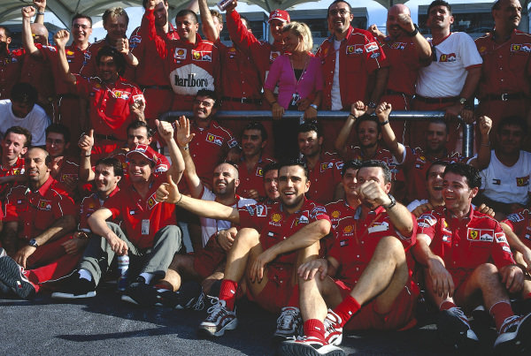 1999 Malaysian Grand Prix.Sepang, Kuala Lumpur, Malaysia. 15-17 October 1999.Eddie Irvine (front) celebrates his 1st position with the Ferrari team and team mate Michael Schumacher (with wife Corinna).Ref-99 MAL 04.World Copyright - LAT Photographic