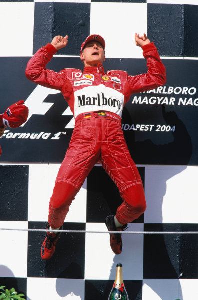 2004 Hungarian Grand Prix  Hungaroring, Hungary. 13th - 15th August.  Michael Schumacher, Ferrari F2004 celebrates on the podium with his famous victory leap. World Copyright:Lorenzo Bellanca/LAT Photographic  Ref:35mm Image:A21