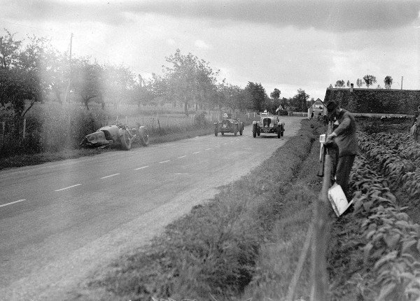 """Le Mans, France. 16 June 1935.""""Michel Paris""""/Marcel Mongin (Delahaye 135, number 7) and Anthony Marsh/HB Guest (Singer Nine) pass the crashed Aston Martin Ulster of Clifton Penn-Hughes/Thomas Fotheringham.Ref-Motor 800/100.World Copyright - LAT Photographic"""
