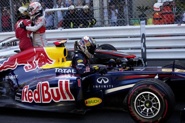 Sebastian Vettel, Red Bull RB7 Renault, arrives in Parc Ferme. Behind, Fernando Alonso hugs Jenson Button.