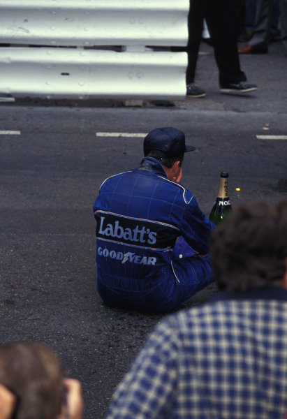 Nigel Mansell sits on the track with a bottle of champagne after the race.