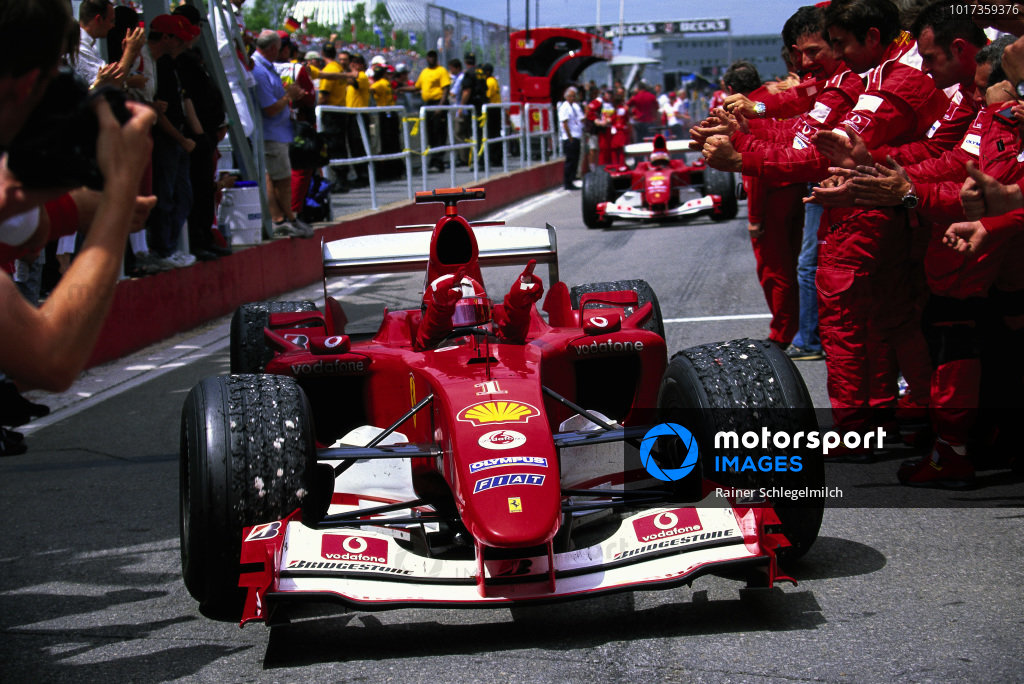 Michael Schumacher, Ferrari F2004 pulls into parc ferme where his team celebrate victory.