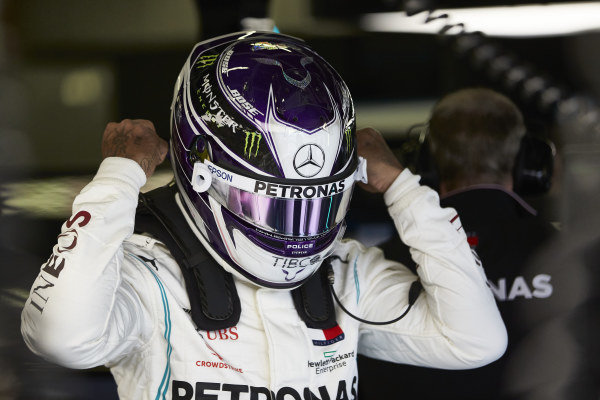 Lewis Hamilton puts on his helmet in the garage as he prepares to drive a Mercedes W09