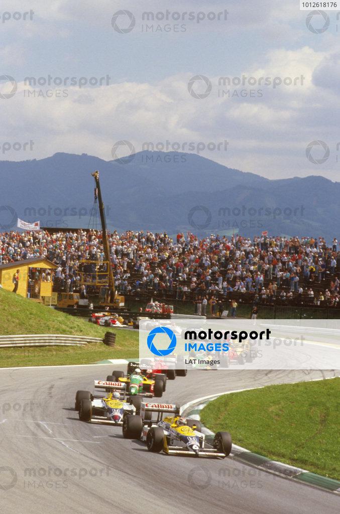 Osterreichring, Zeltweg, Austria. 14-16 August 1987.Nelson Piquet leads teammate Nigel Mansell (both Williams FW11B Honda's), Teo Fabi (Benetton B187 Ford) and Gerhard Berger (Ferrari F187) at the start. Ref-87 AUT 04.World Copyright - LAT Photographic