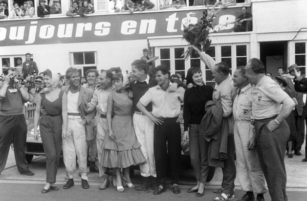 Peter Collins and Stirling Moss, stand with Ron Flockhart and Ninian Sanderson, Wilkie Wilkinson and David Murray, after the race.