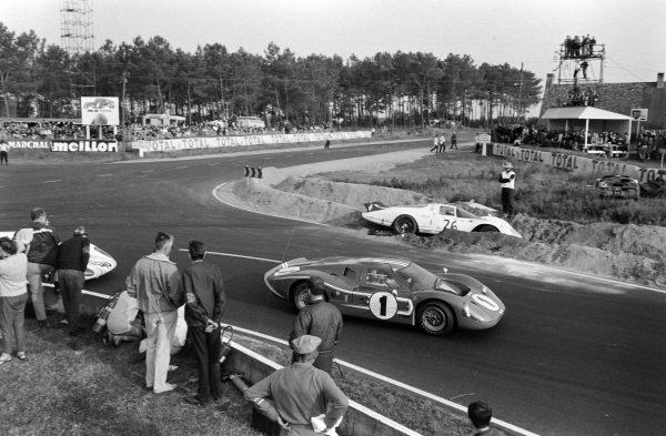 Dan Gurney / A.J. Foyt, Shelby-American, Ford GT40 Mk.IV, passes the crashed car of Chuck Parsons / Ricardo Rodriguez-Cazados, North American Racing Team, Ferrari 365P2.