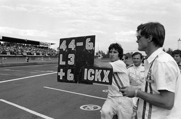 A McLaren mechanic holds out a pit board.