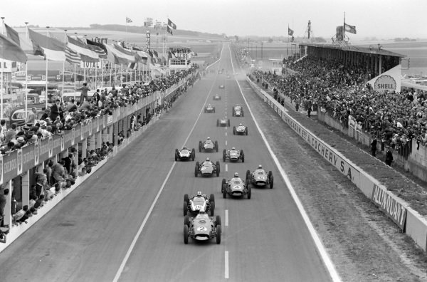 Phil Hill, Ferrari 246, Jack Brabham, Cooper T53 Climax, Wolfgang von Trips, Ferrari 246, and Willy Mairesse, Ferrari 246, lead the field away at the start.