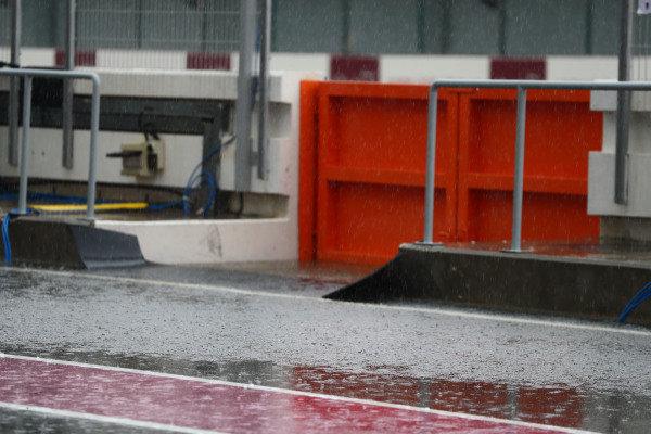 Rain in the pitlane .