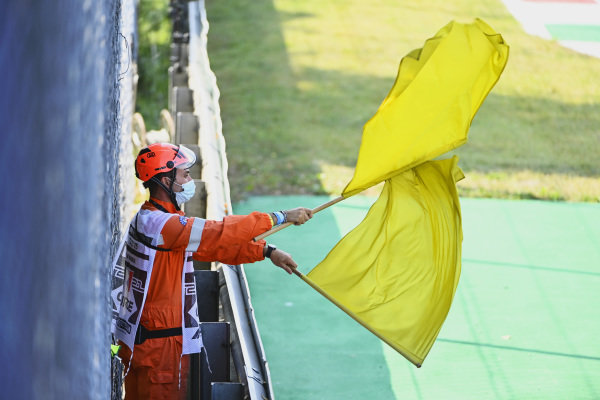 A marshal waves double yellow flags