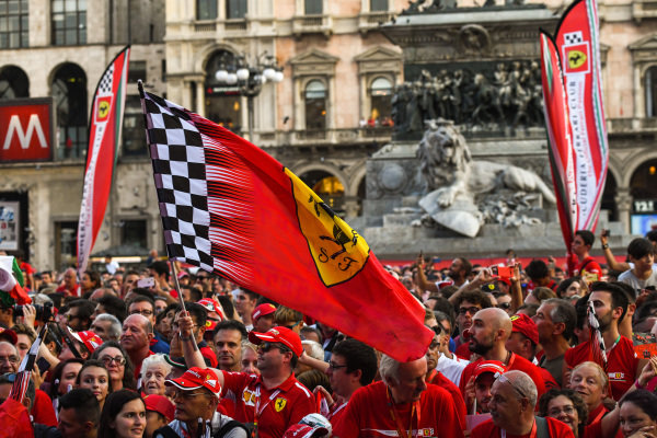A Ferrari flag waves amidst the crowd