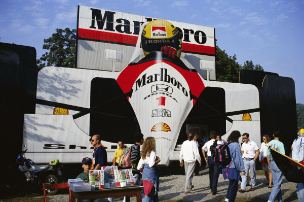 A large billboard depicting Ayrton Senna's McLaren MP4-7A Honda in the paddock.