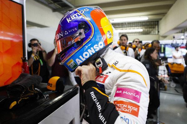 Fernando Alonso, McLaren, adjusts his crash helmet.