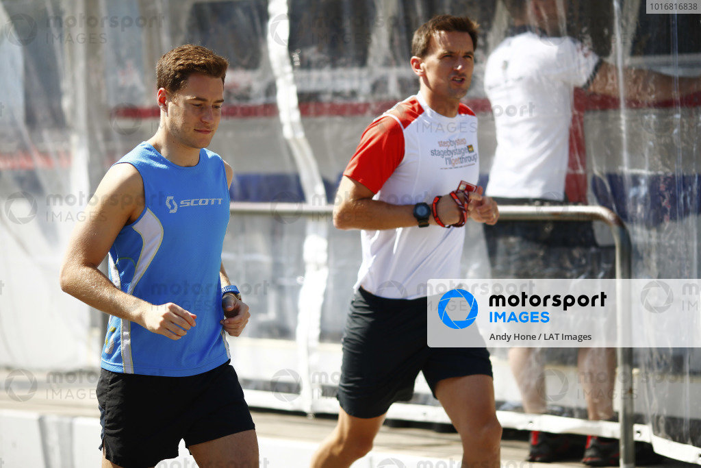 Stoffel Vandoorne, McLaren, jogs in the pit lane with his trainer.