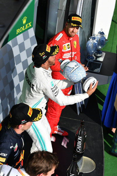 Lewis Hamilton, Mercedes AMG F1, 1st position, tosses his trophy in the air in celebration alongside Max Verstappen, Red Bull Racing, 2nd position, and Sebastian Vettel, Ferrari, 3rd position