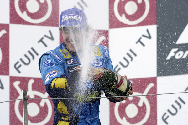 Fernando Alonso sprays champagne on his team below.