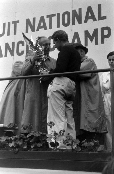 Peter Collins receives the winner's trophy.