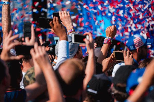 The crowd celebrate below the podium