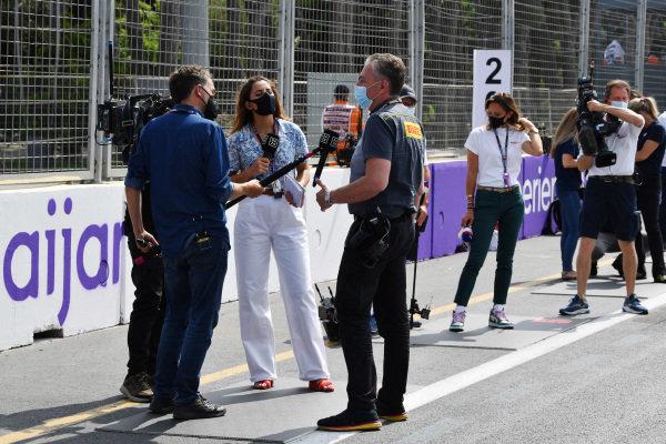 Television reporters talk to Mario Isola, Racing Manager, Pirelli Motorsport. Mara Sangiorgio of Sky Italia waits on