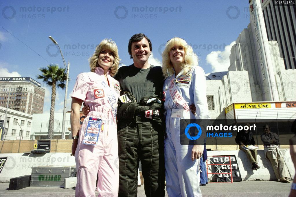 Alan Jones with two 'Miss Toyota Grand Prix'.