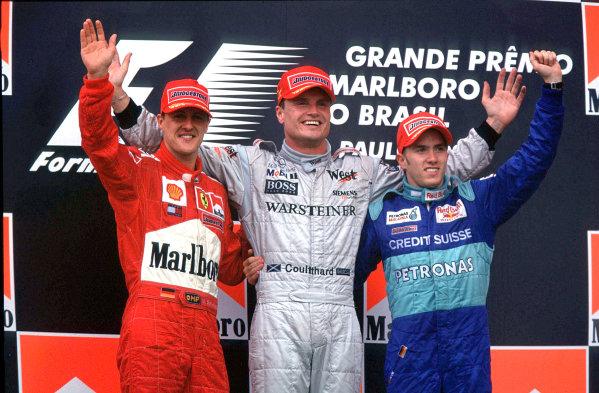2001 Brazilian Grand Prix. Interlagos, Sao Paulo, Brazil.  30/3-1/4 2001. David Coulthard (McLaren Mercedes) 1st position, Michael Schumacher (Ferrari) 2nd position and Nick Heidfeld (Sauber Petronas) 3rd position on the podium. World Copyright - Clive Rose/LAT Photographic  ref: 35mm A04