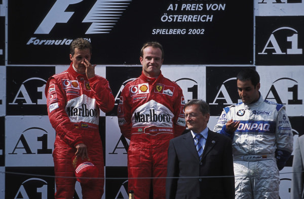 Rubens Barrichello, Ferrari, stands in 1st position after controversially moving over for Michael Schumacher, standing in 2nd position, on the podium. Juan Pablo Montoya, 3rd position, looks at his hand as fans make their displeasure known.
