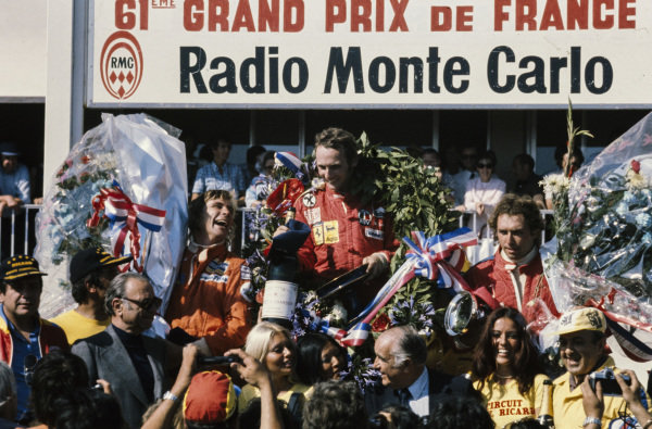 Niki Lauda celebrates victory on the podium with James Hunt, 2nd position, and Jochen Mass, 3rd position.