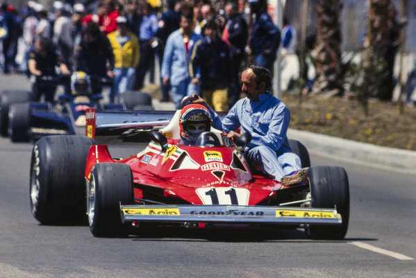 Niki Lauda, Ferrari 312T2 taxis one of his mechanics to the grid.