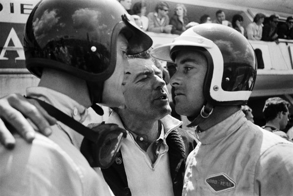 Carroll Shelby talks to his drivers, Dan Gurney and Bob Bondurant, in the pits.