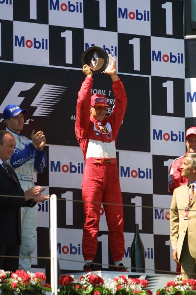 2001 French Grand Prix - RaceMagny-Cours, France. 1st July 2001Michael Schumacher, Ferrari F2001, celebrates his 50th win , by lifting the trophy in triumph.World Copyright - LAT Photographicref: 8 9 MB Digital File only