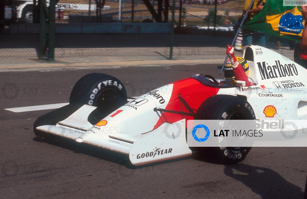 1992 Hungarian Grand Prix.Hungaroring, Budapest, Hungary.14-16 August 1992.Ayrton Senna (McLaren MP4/7A Honda) carries the Brazilian flag after his win.Ref-92 HUN 15.World Copyright - LAT Photographic