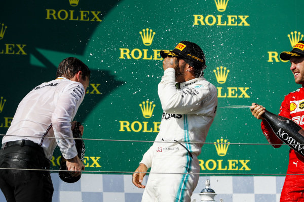 Lewis Hamilton, Mercedes AMG F1, 1st position, and Sebastian Vettel, Ferrari, 3rd position, celebrate on the podium
