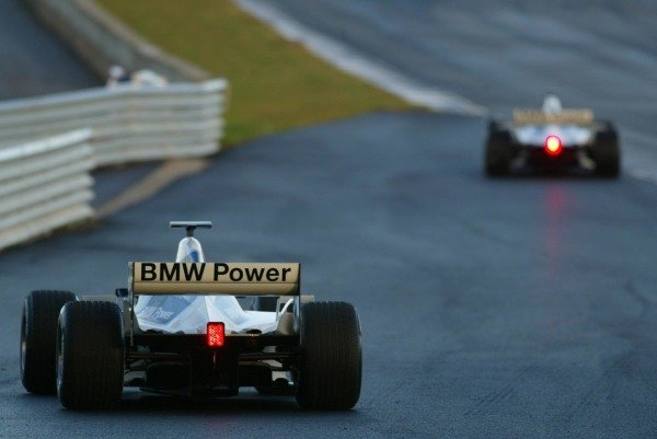 Ralf Schumacher (GER) Williams BMW FW24  drives past Marc Gene (ESP) Williams Test Driver 
