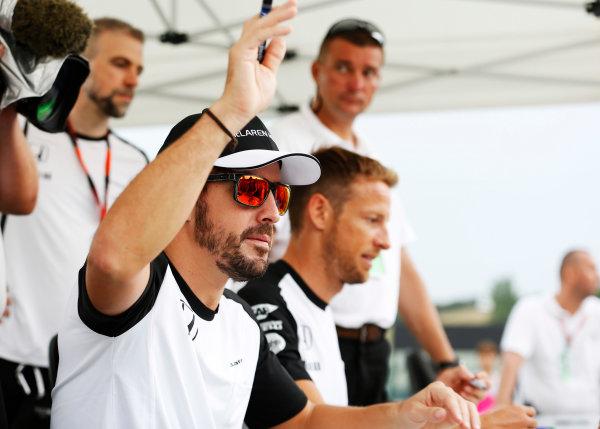 Hungaroring, Budapest, Hungary. Thursday 23 July 2015. Fernando Alonso, McLaren, and Jenson Button, McLaren, sign autographs for fans. World Copyright: Charles Coates/LAT Photographic ref: Digital Image _J5R0929