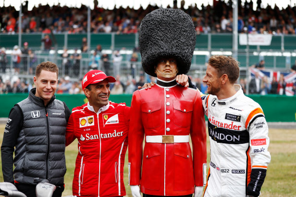 Silverstone, Northamptonshire, UK.  Thursday 13 July 2017. Stoffel Vandoorne, McLaren, MarcGene of Ferrari and Jenson Button, McLaren, with a dummy Scots Guard. World Copyright: Glenn Dunbar/LAT Images  ref: Digital Image _31I2355